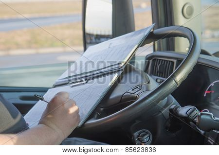Truck Driver Is Writing In The Documentation.