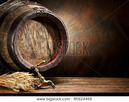 Still life: old wooden pin of beer and wheat on the table in the cellar.