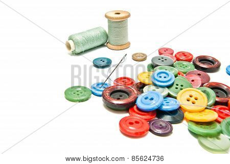 Buttons And Spools Of Thread On White