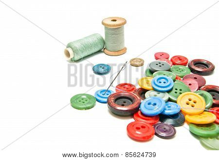 Plastic Buttons And Spools Of Thread On White