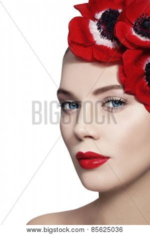 Portrait of young beautiful woman with clean make-up, red lips and red flowers in her hair over white background, copy space