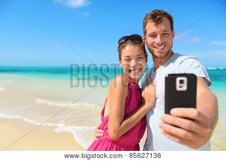 Beach vacation couple taking selfie photograph using smartphone relaxing and having fun holding smart phone camera. Young beautiful multicultural Asian Caucasian couple on summer beach.