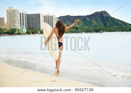 Beach fun - Happy freedom surfer woman going surfing in Waikiki beach, Honolulu city, Oahu, Hawaii, USA. Hawaiian surf girl heading for waves with surfboard living healthy active lifestyle, rear view.