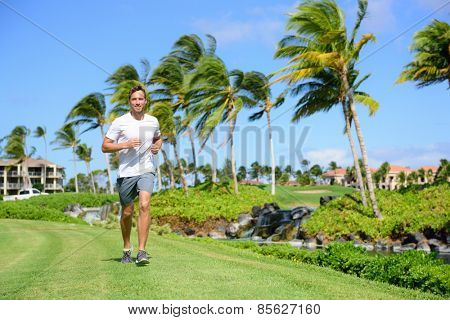 Outdoor exercise man running on grass in city park, resort area or upscale community. Happy young male runner staying fit exercising and living a healthy lifestyle training outside in summer nature.