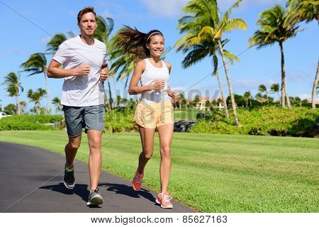 Sport couple exercising running outside on street in summer. Happy active young fit adults jogging together with tropical background in city park or resort road. Asian and Caucasian people.