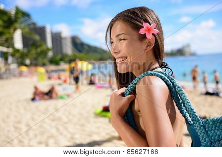 Asian tourist woman on vacation in Waikiki beach, Hawaii, USA. Pretty girl holding beach bag walking on famous touristic area in Honolulu city, Oahu, Hawaii, USA. Summer travel holiday concept.