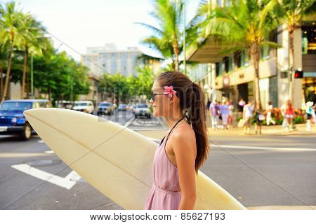 Surfer woman walking in city with surfboard to go surfing. Urban Hawaiian surf concept. Asian girl holding surf board crossing street to go to the beach. Waikiki, Honolulu city, Oahu, Hawaii, USA.