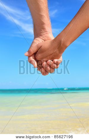 Love - romantic couple holding hands on beach. Close up of hands of young lovers enjoying romance on summer vacation travel holidays.