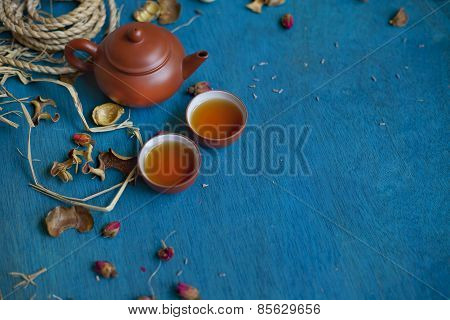 Teapot With Two Cups On Blue Wooden Table