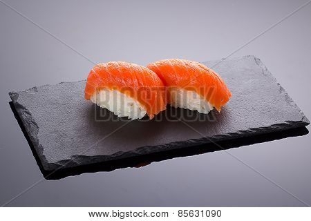 Salmon Sushi Nigiri On A Stone Plate Over Black Backround