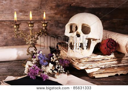 Still life with human skull, retro book and candlelight on wooden table, closeup