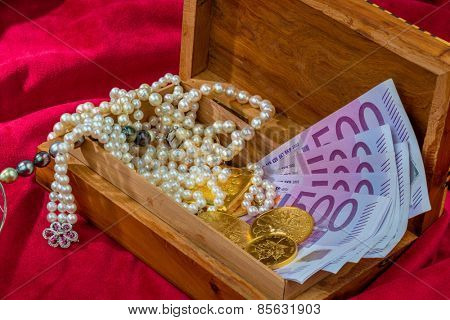 gold coins and bars with decorations on red velvet. photo icon for wealth, luxury, wealth tax.