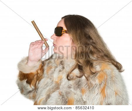 Woman with fur coat and smokes a cigar