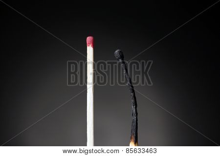 Match and burnt match on dark background