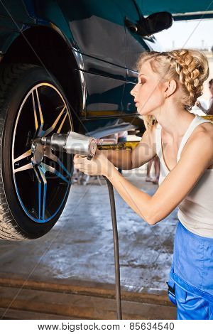 Female Technician Replaces The Wheel Of The Vehicle In Service