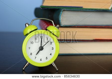 Stack of books with alarm clock on wooden desk and colorful background