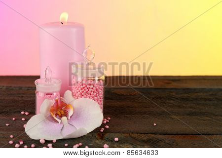 Composition with candle and bottle of sea salt on table on bright background