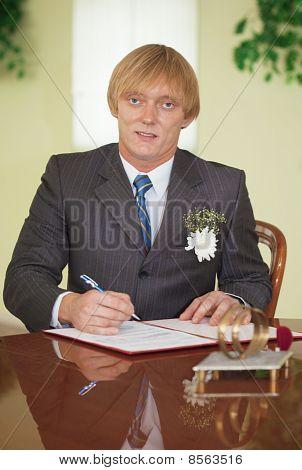 Groom Puts Signature On Registration Document