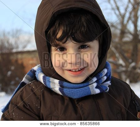 Little Boy Playing Outdoors With Snow