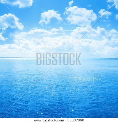 Blue sea and sky with white clouds.