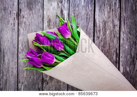 Bouquet Of Purple Tulips On A Rustic Background