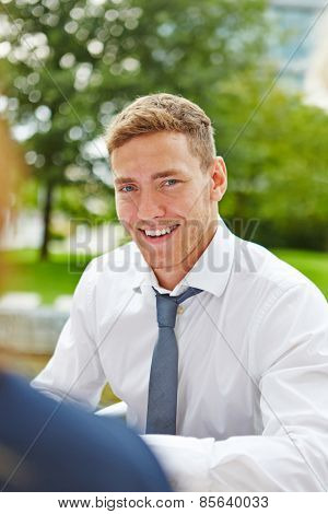 Smiling young business man sitting outdoors in summer