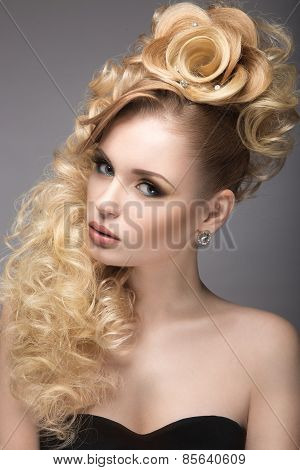 Beautiful blonde girl in evening dress with an unusual hairstyle in the form of roses and bright mak