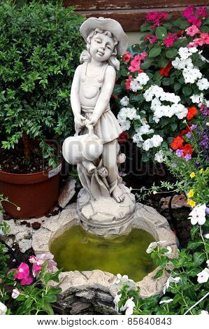 Garden Sculpture. Girl With Watering Can