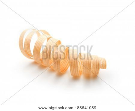 Nicely shaped thin wood shaving isolated on white. Shallow depth of field.