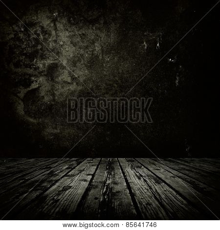 Dark room with stone or masonry wall and grungy old  wooden floor.