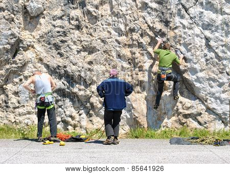 Three People Climbing Up A Rock Face