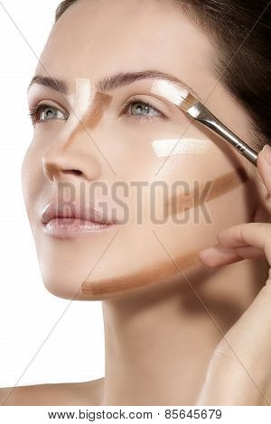 Beautiful Model Applying Foundation With A Brush