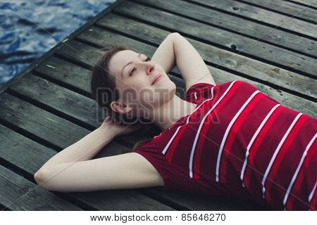 Young woman in casual clothing resting and looking on sky outdoors on wooden bridge portrait.