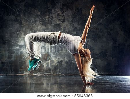 Young woman modern dancer. On dark stone wall background.