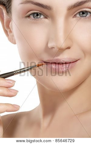 Beautiful Model Applying Lip Gloss With A Brush