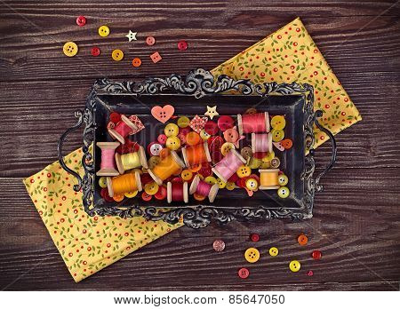 Sewing items in yellow and red arranged on a vintage tray