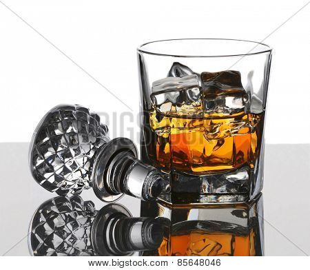 Glass of scotch on the rocks with decanter stopper and reflections. Vertical composition with copy space over white background.