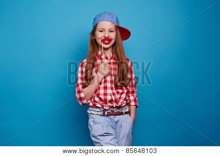 Funny girl keeping red lips on a stick