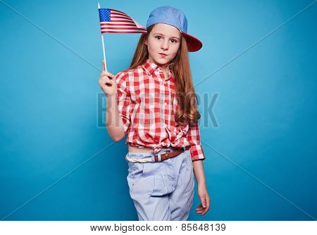 Beautiful girl holding American flag on a stick