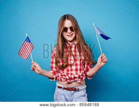 Little girl holding two different flags on a stick