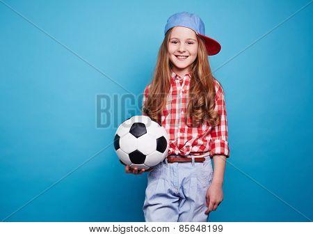 Smiling girl keeping white black ball