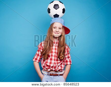 Smiling girl holding soccer ball on her head