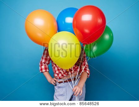Little girl hiding behind bunch of colorful balloons