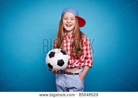 Smiling girl keeping soccer ball in her hands