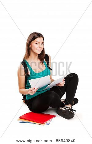 Young teen student sitting on floor with backpack reading a book