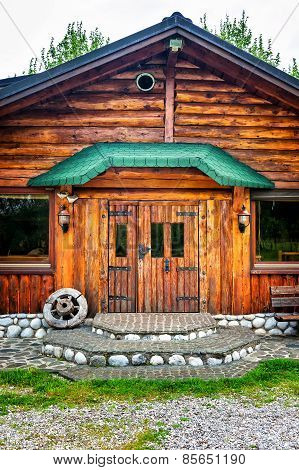 Wooden Brown Cottage In The Countryside With A Wheel On The Porch