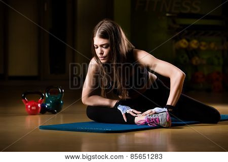 Attractive female athlete stretching on yoga mat in gym.Young and athletic girl in a gym.