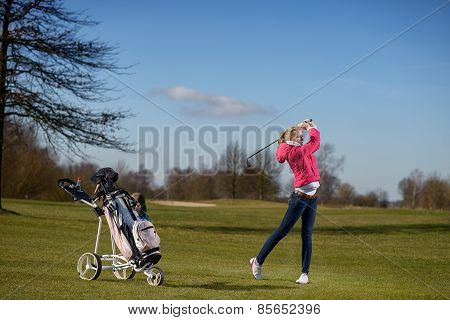 Young Female Golfer Playing On The Fairway