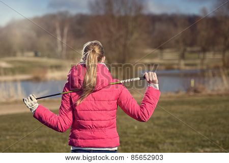 Rear View Of Female Golfer With Club On Shoulder