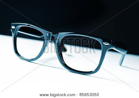 a pair of black plastic-rimmed eyeglasses on a white surface, and a black background